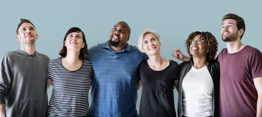 a diverse group of men and women stand arm in arm smiling in a friendly way