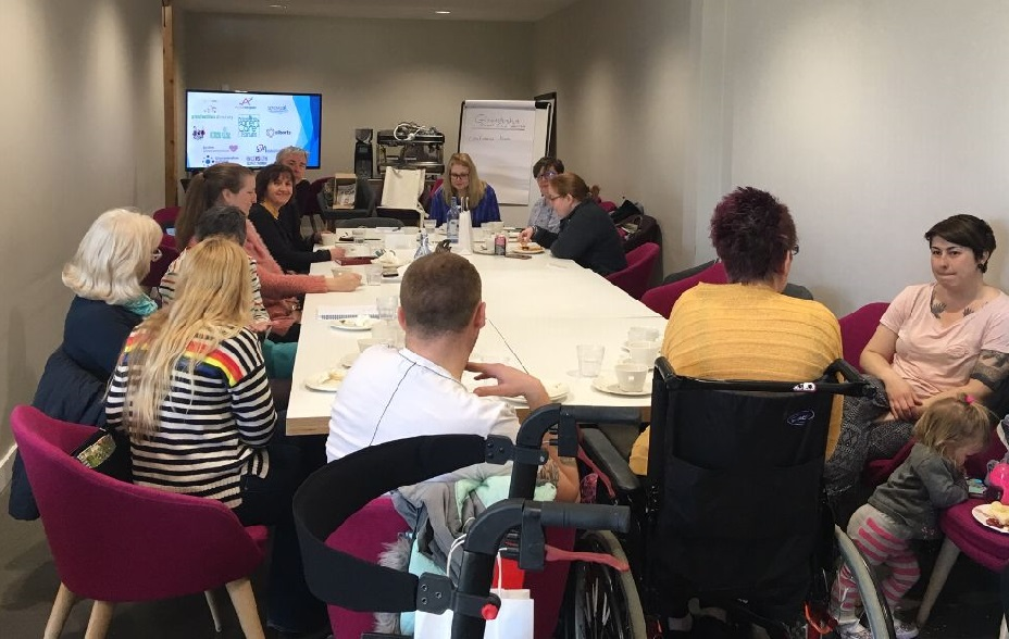 a group of parents sit round a table listening to a presentation, one lady is in a wheelchair, a child is standing by one mum